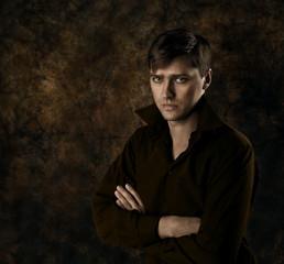 Handsome man sitting over dark brown gothic background. Seriousl