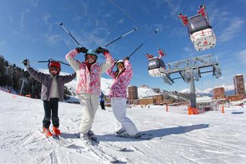Trois jeune skieur devant les télécabines
