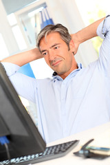 Man relaxing in office with stretched arms