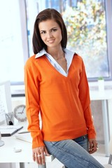 Pretty office worker smiling in orange pullover