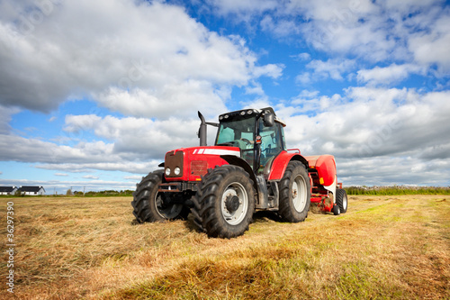 Wall mural tractor collecting haystack in the field, panning technique