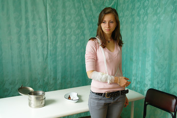 A sad girl with a bandaged patient bandaged hand