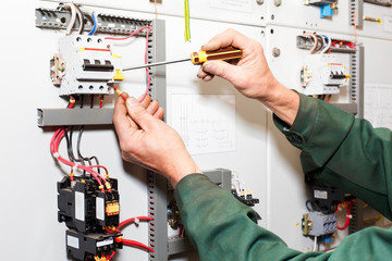 Electrician`s hands working with screwdriver in cables and wires