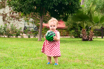 child playing with ball in garden