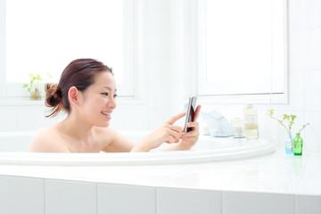 入浴しながらスマートフォンを使う女の子