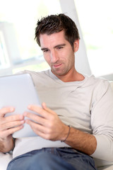 Man relaxing at home with electronic tablet