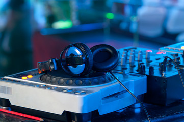 Dj mixer with headphones at a nightclub
