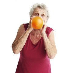senior woman blowing balloon