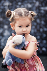 A little girl half-breed with a toy