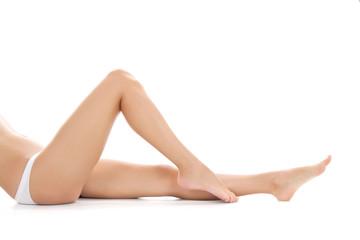 beautiful female legs barefoot lying on white background