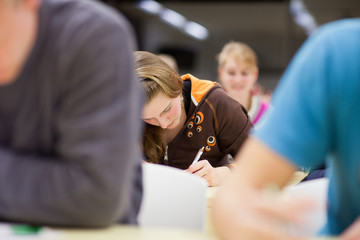pretty, female college student sitting in a classroom