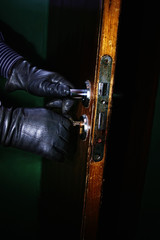 hands in leather gloves of a burglar opening a door