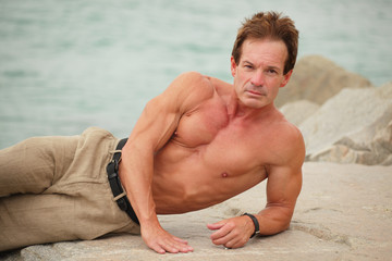 Image of a handsome man laying on the rocks
