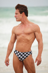 Image of an attractive bodybuilder posing on the beach