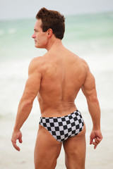 Back view of a bodybuilder at the beach