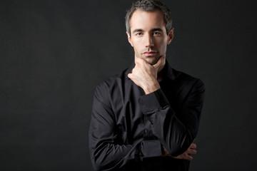 Handsome man posing in black shirt on dark background.