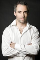 Handsome man posing in white shirt on dark background.
