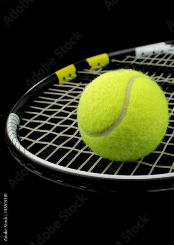 Wall mural Tennis racket and tennis bal on black background