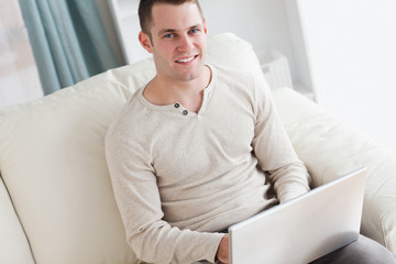 Smiling man using a laptop while sitting on a couch