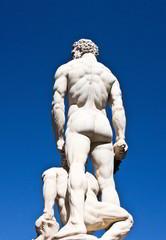 Behind statue of Hercules on blue sky