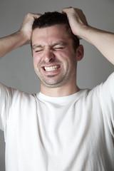 A man grabbing his hair and screaming.