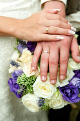 Just married couple hands. Rings and flowers