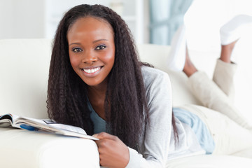 Woman with booklet on sofa