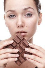 Beautiful young woman with chocolate over white backgound