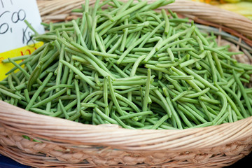 Green string beans in woven basket close-up
