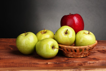 juicy sweet apples in basket on wooden table on gray background