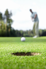 A man scores ball in the hole