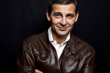 portrait of a cool mature man with leather jacket over black bac