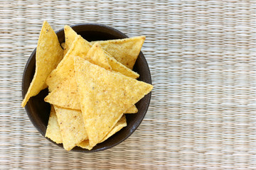Mexican tortilla chips in brown bowl on white background