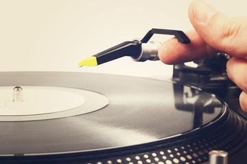 hand put the tonearm on vinyl record