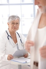 Senior female doctor looking at patient