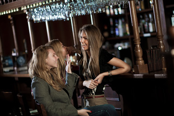 Three happy young women in a nightclub sitting at the bar