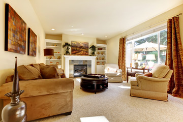 Living room with art, large window, sofas and fireplace.