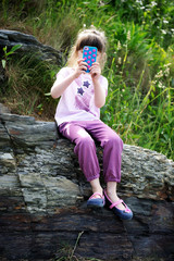 Little girl with mobile phone on rocks
