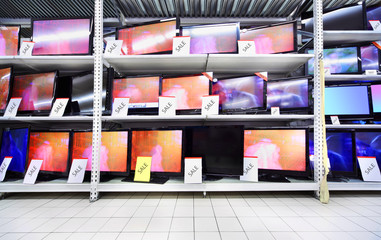 Plasma TVs with big diagonal stand on shelves in large store