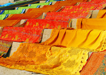 Foto op Canvas Marokko Bright orange and red saris draped on stairs to dry in the sun