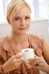 Smiling blonde drinking cappuccino