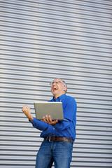 jubelnder mann mit laptop
