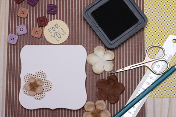 hand made scrapbooking post card and tools lying on a table.