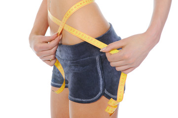 Young sports woman measuring waist.
