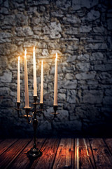 Candleholder in front of old Wall