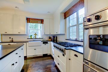 Luxury white kitchen with dark floors.