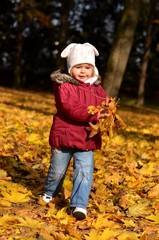 Little girl in a red coat at autumn holding leaves