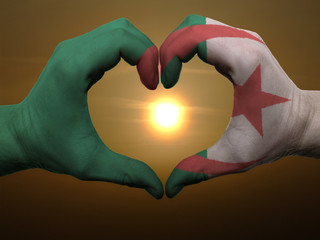 Foto op Aluminium Algerije Heart and love gesture by hands colored in algeria flag during b
