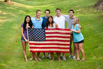Group of diverse college students holding American flag