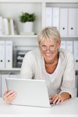 lächelnde ältere frau mit laptop im büro